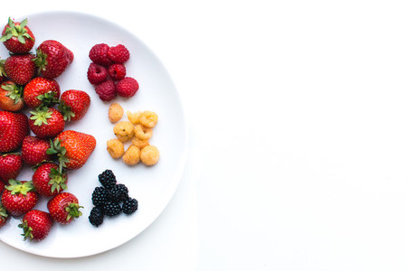 Aerial shot of colorful healthy fresh berries on a plate on a wh