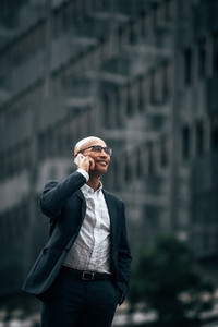 Business executive talking over mobile phone standing outdoors