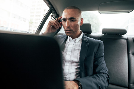 Businessman using laptop sitting in car