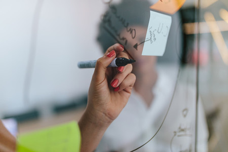 Woman writing on transparent board