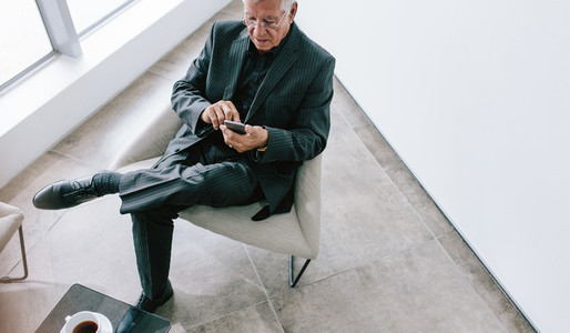 Senior businessman texting with mobile phone