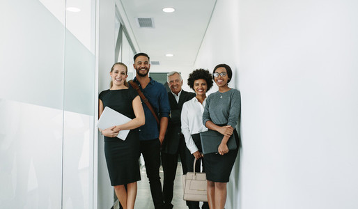 Multiracial corporate professionals in office hallway