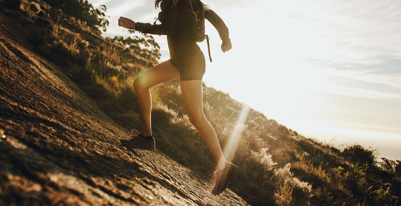 Woman running up a rocky mountain slope