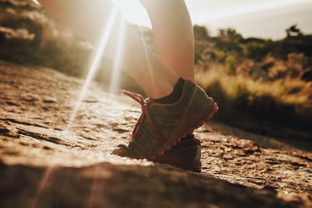 Female trail runner standing in sunlight
