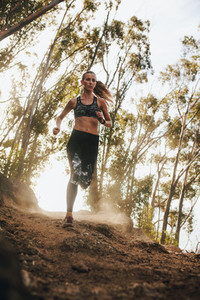 Female runner running on a rocky mountain trail