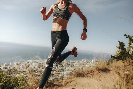 Sportswoman sprinting over rocky trail