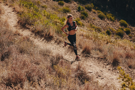 Woman running through mountain path