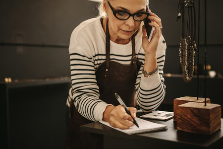 Female jeweler talking on mobile phone and making notes