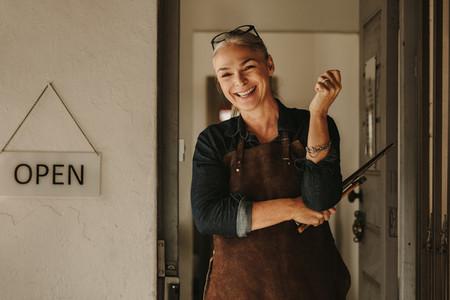 Smiling jewelry maker at workshop entrance