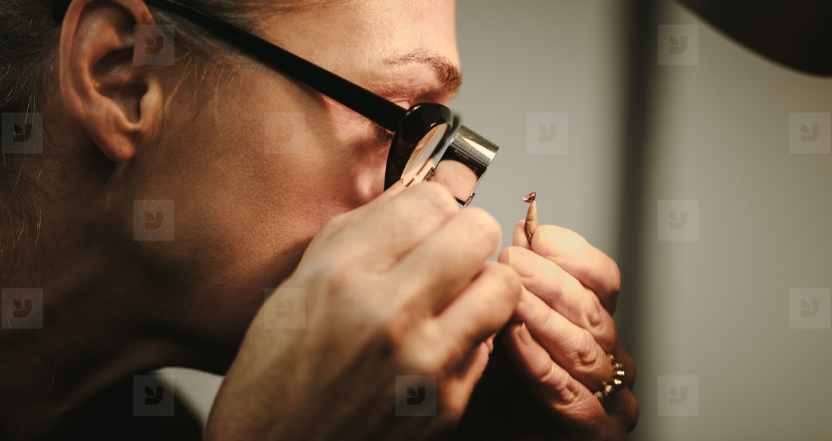 Senior woman goldsmith checking quality of diamond