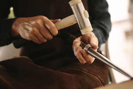 Jeweler working with the hammer on silver ring