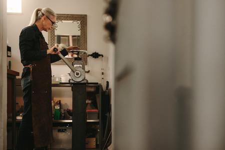 Mature woman working in goldsmith workshop