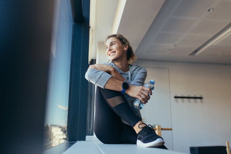 Woman relaxing after workout sitting in a pilates gym