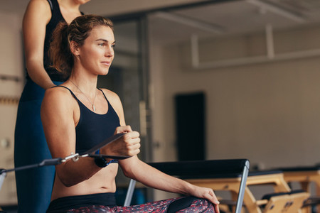 Woman at a pilates gym pulling stretch bands