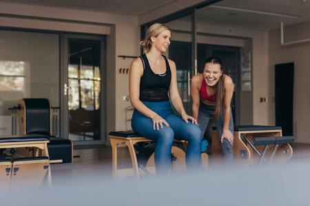 Happy pilates women at a gym taking a break during workout