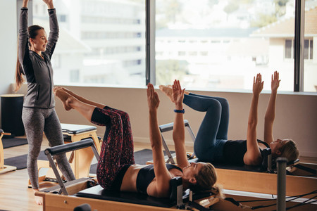Pilates instructor training women at a gym