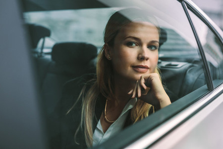 Female executive travelling by a car