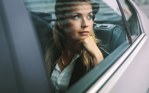 Female business executive travelling by a cab