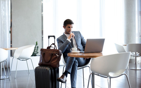 Businessman in airport business lounge with laptop