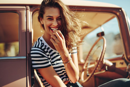 Beautiful young woman laughing in the car