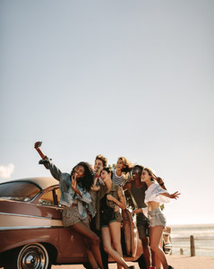 Multi ethnic friends taking a selfie near the car