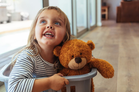 Girl sitting in washing basket with her teddy