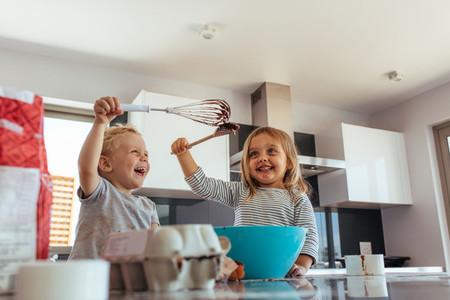 Siblings enjoying baking in kitchen