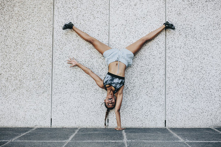 Fitness woman standing upside down on one hand