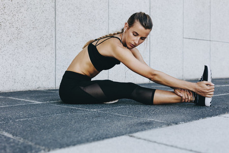 Female runner doing stretching exercises sitting outdoors