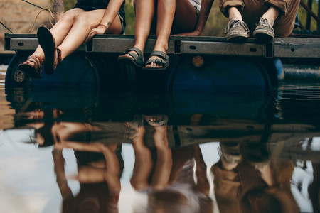 Friends sitting on a floating dock on a lake