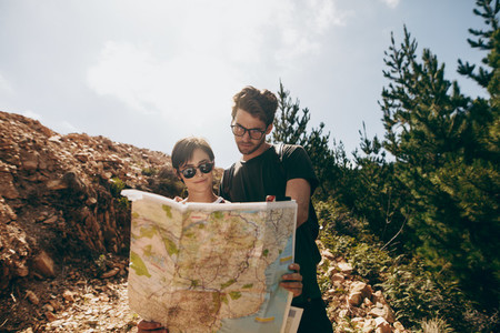 Explorer couple looking at a map for navigation
