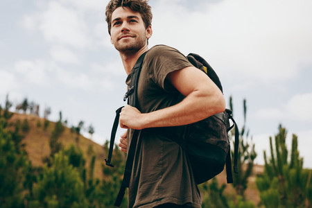 Man walking through a forest wearing a backpack