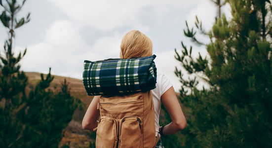 Rear view of a explorer woman carrying travelling kit