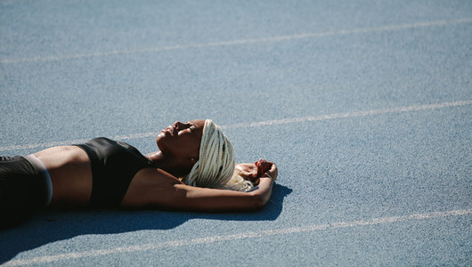 Female sprinter lying on running track after workout