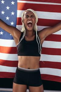 Female athlete celebrating victory holding american flag