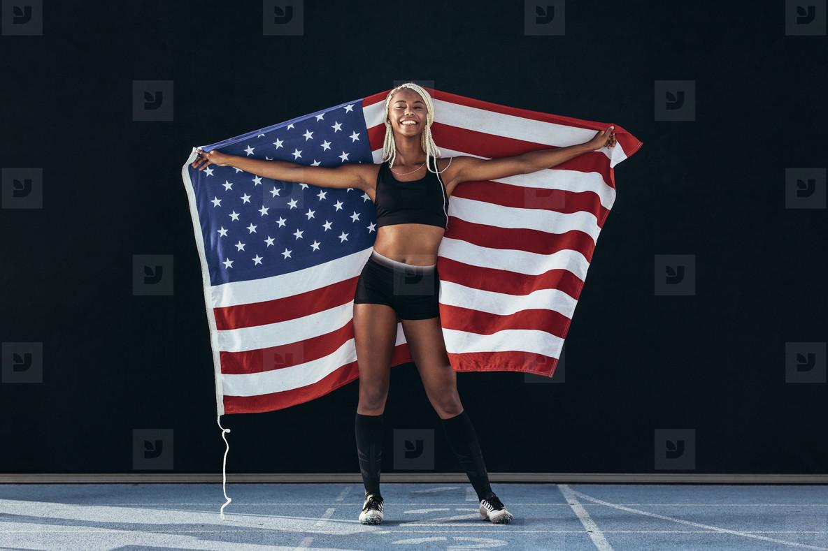 Female athlete standing on running track holding american flag