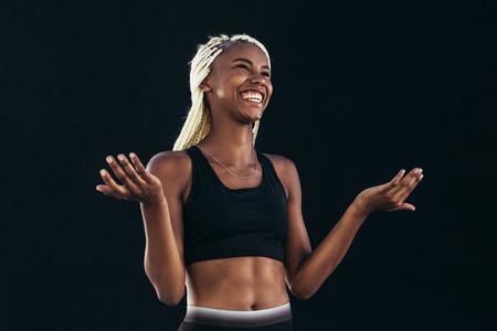 Smiling female athlete standing against black background