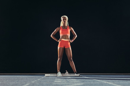Female athlete standing on a running track