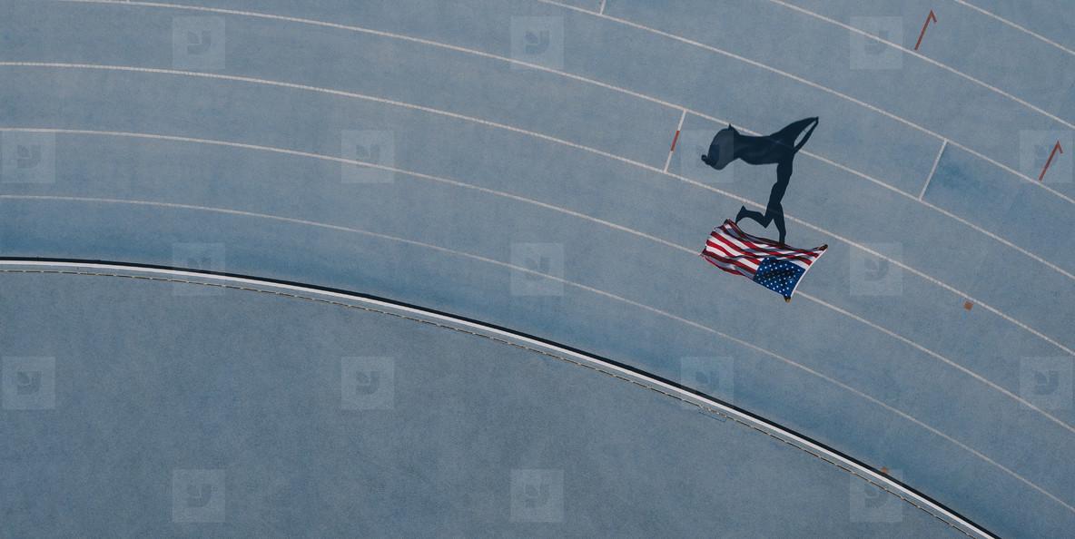 Athlete running on the track holding flag celebrating win