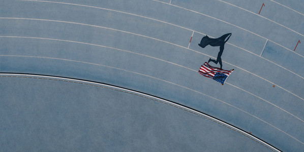 Athlete running on the track holding flag celebrating win