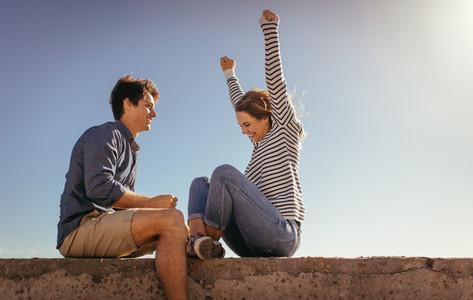Happy couple having fun sitting on a sea wall