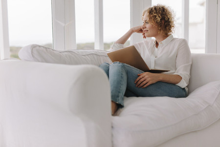 Woman sitting on couch at home with a laptop