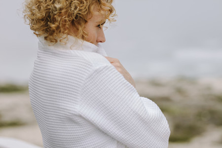 Close up of a woman in white coat looking at the sea