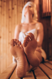 Woman sitting in a wooden spa taking steam bath