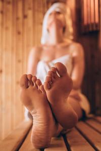 Woman sitting in a wooden spa taking steam bath