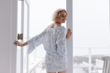 Woman standing near the balcony door in the morning