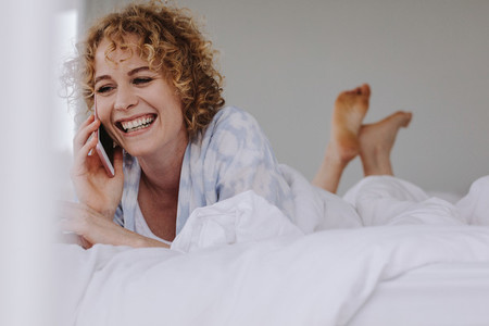 Woman talking on mobile phone lying on bed