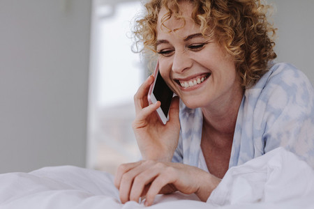 Close up of a smiling woman talking over mobile phone lying on b