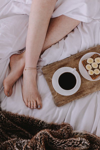 Top view of a woman in bed with breakfast