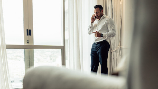 Businessman making a phone call from hotel room